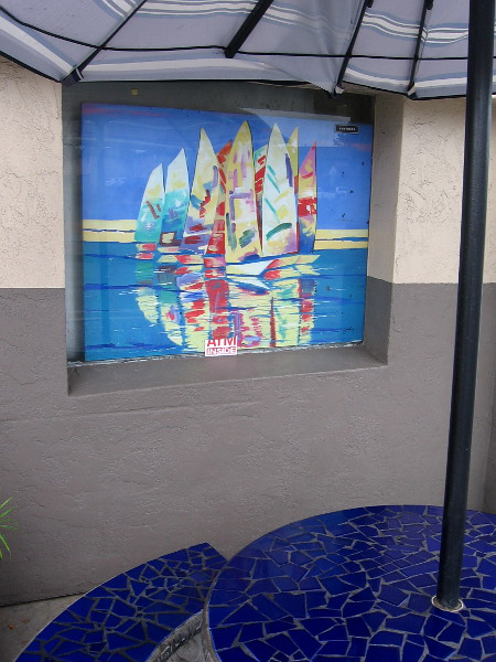 Colorful sailboats by an outdoor table.