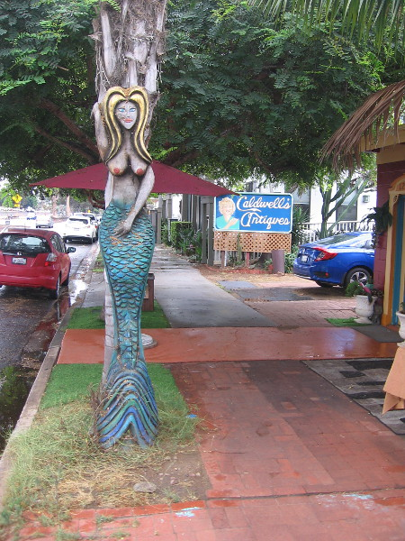 A very tall carved mermaid by the sidewalk.