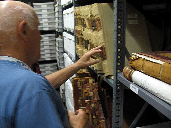 Archivist Jerry Handfield shows visitors shelves of old canvas and leather-bound books, including some that contain City Council Resolutions.