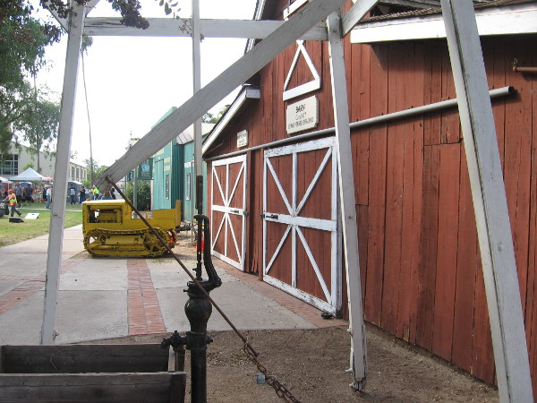 Looking backward through the windmill, we see an old tractor parked in front of the Penner Barn.