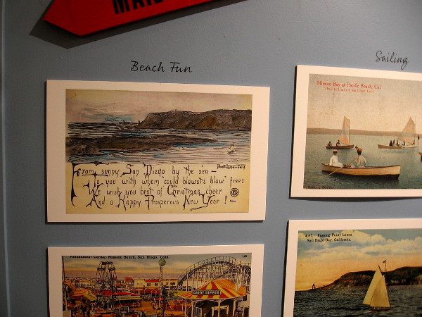 Diverse themes in the postcard exhibit include beach fun and sailing.