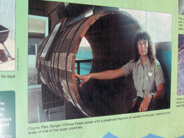 San Diego County Park Ranger shows a section of wooden flume pipe.