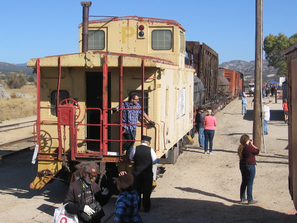 Visitors check out a caboose and more railroad cars to one side of the historic Campo train depot.