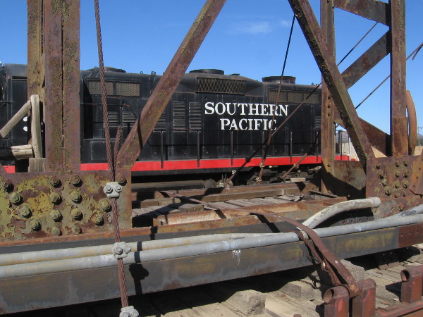 A cool photo of a nearby Southern Pacific locomotive through the transported turntable.