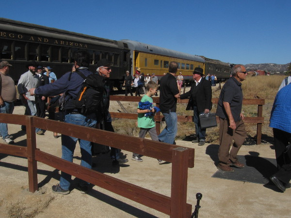 Passengers disembark from the day's first excursion train and arrive at the outdoor venue for the gold spike event, near the museum's Display Building.