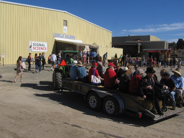 A hay ride pulls up to the Display Building area.
