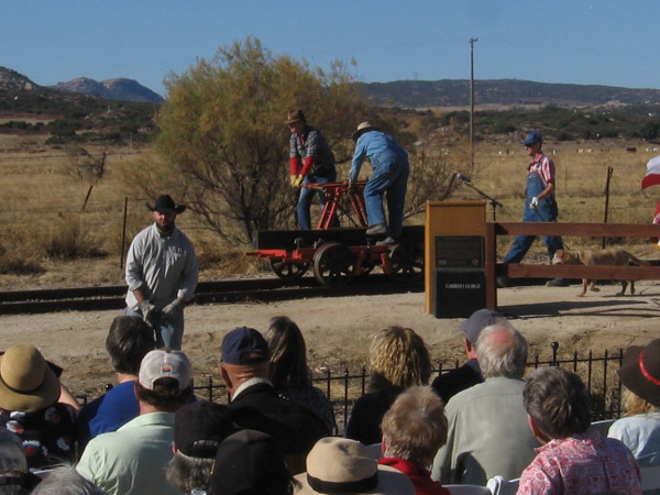 The gold spike reenactment begins. Railroad workers arrive by handcar.