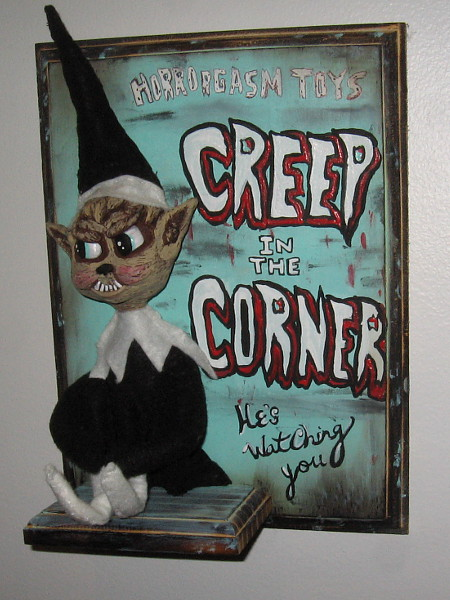 Creep in the Corner by artist Jennifer Cooksey. Mixed media sculpture and acrylic. A sinister Elf on the Shelf.