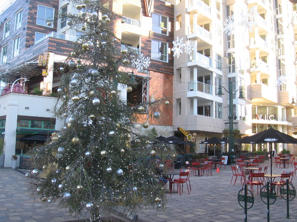A silvery Christmas tree and white snowflakes near the piazza's many outdoor tables and chairs.