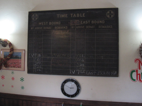 A board on the wall shows arrival times for Amtrak and the Coaster. The active Carlsbad Village train station is one block north.