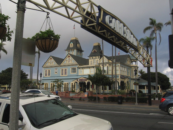 Photo of the grand Twin Inns building beyond the landmark Carlsbad sign on Carlsbad Boulevard, which is a segment of Historic Route 101.