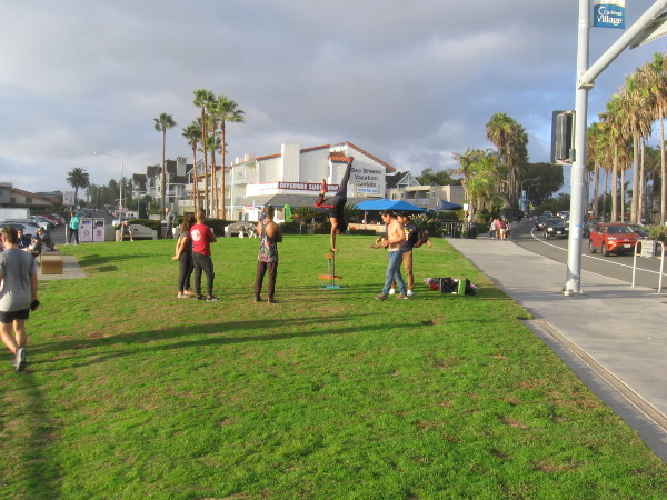 Someone performs a handstand in a grassy park that overlooks the beach in Carlsbad Village.