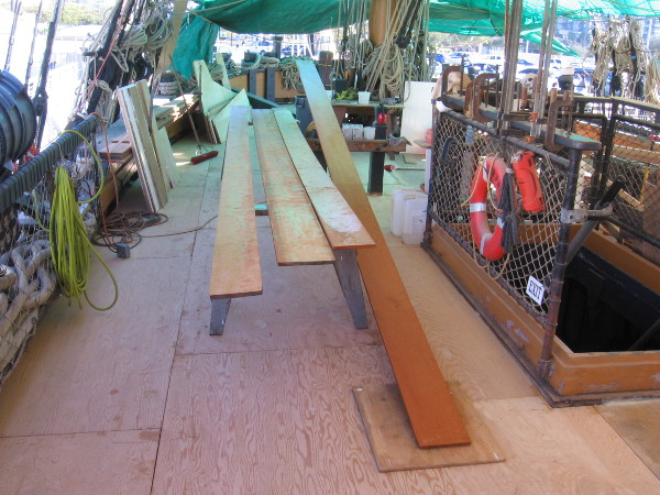 Lumber is prepared on the main deck of HMS Surprise during the famous tall ship's re-decking project.
