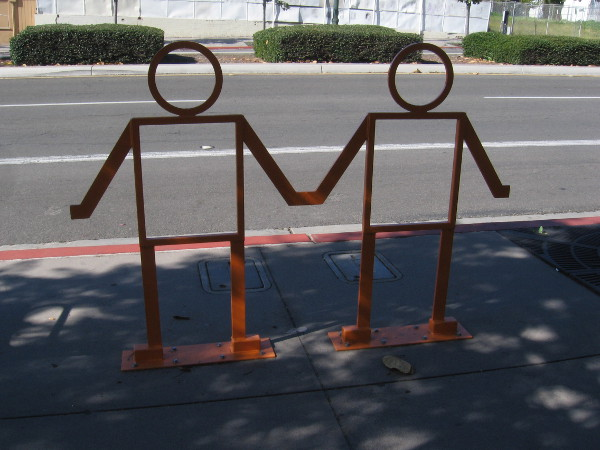Sculpture of two people holding hands on sidewalk.