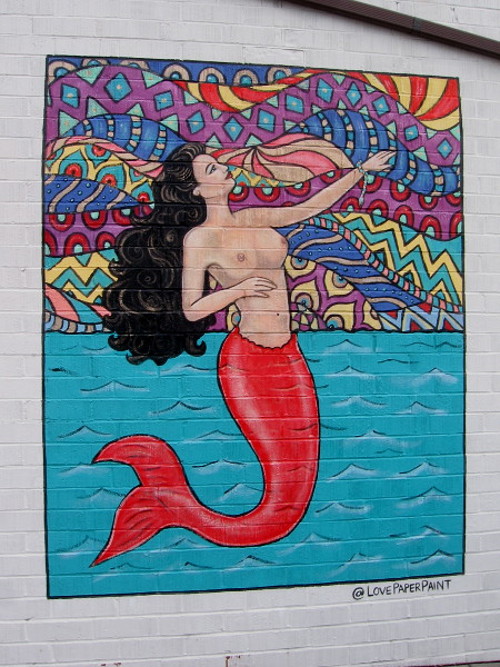 A mermaid mural by @LovePaperPaint (Katie Gaines) is inspired by the traditional La Sirena image in Mexican Lotería.