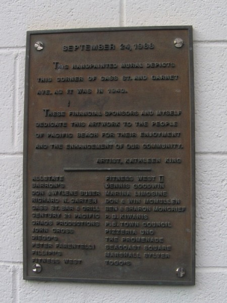 Plaque explains the mural depicts the corner of Cass Street and Garnet Avenue as it was in 1943.