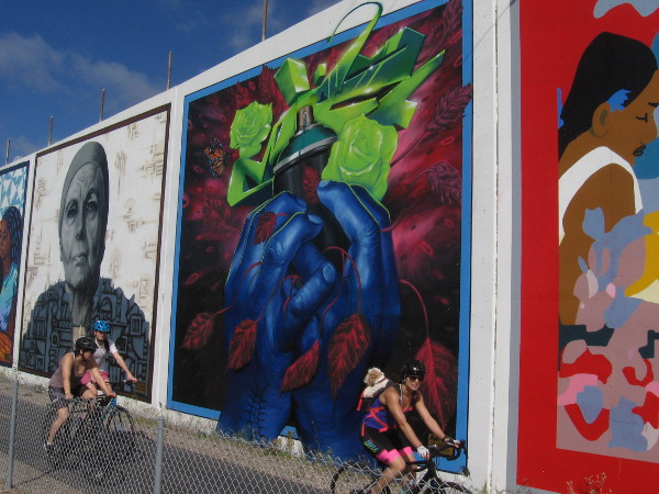 People bicycle past huge colorful murals painted along the Bayshore Bikeway in Chula Vista.