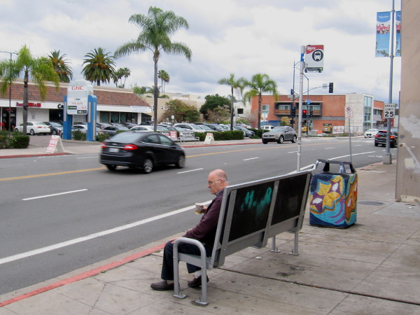 An older gentleman waits for a bus on University Avenue in Hillcrest.