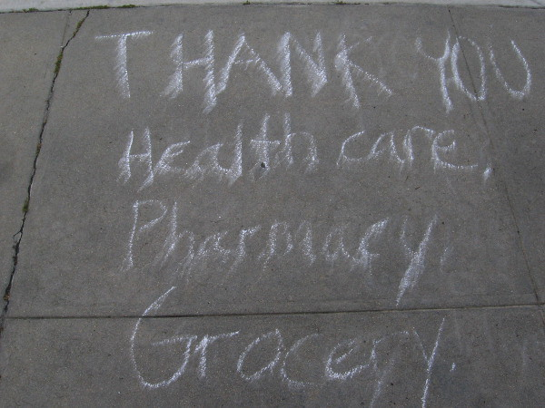 Written in chalk on the sidewalk: Thank you healthcare, pharmacy, grocery...