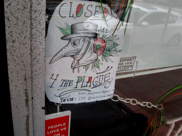 A tattoo parlor has a graphic in their window. Closed 4 the plague.