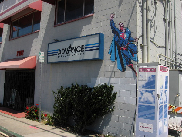 A superhero who resembles Superman flies from what might be San Diego's last phone booth.
