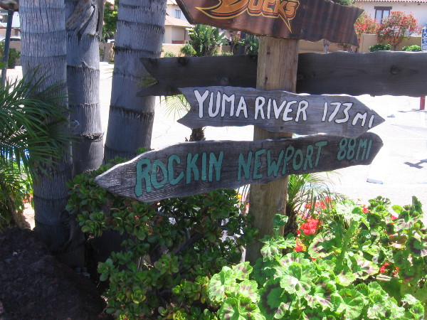 Signs by the parking lot of Rockin' Baja point to different distant destinations.