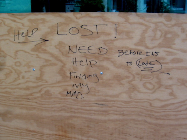 Written on plywood by the sidewalk: Help. Lost! Need help finding my mind. Before it's too late.