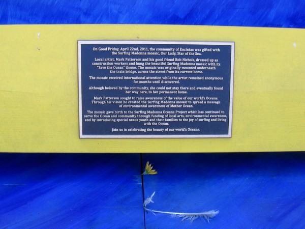 A plaque details the history of the Surfing Madonna.