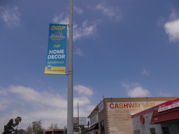 Banner on lamp post invites people to Shop for Home Decor in the Morena District.