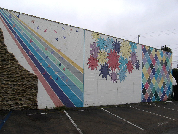 Mural on parking lot wall by Treelogy Cafe Restaurant.