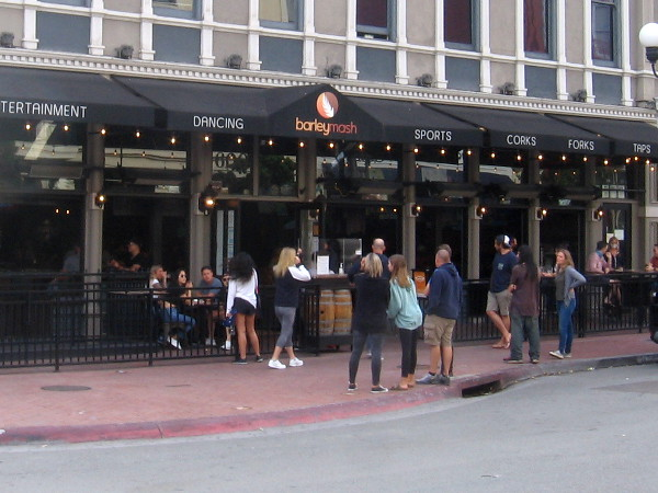 People gather in front of Barleymash as some restaurants reopen in the Gaslamp for dining during the coronavirus pandemic.