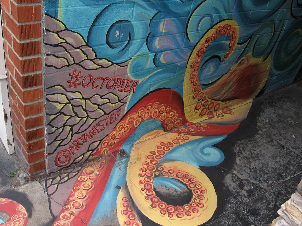 Bottom of the alley mural, with an octopus tentacle wearing a beach sandal. #octopier by @artanystef.