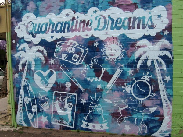 Quarantine Dreams mural in La Jolla. When quarantined due to coronavirus, you can't travel, dine, date, surf, play sports, or even play outside with the dog. Hang in there!