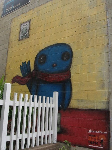 A fun blue character painted on another nearby wall by Gloria Muriel.