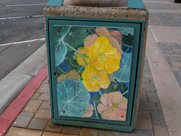 Another trashcan down the sidewalk has been painted with flowers.