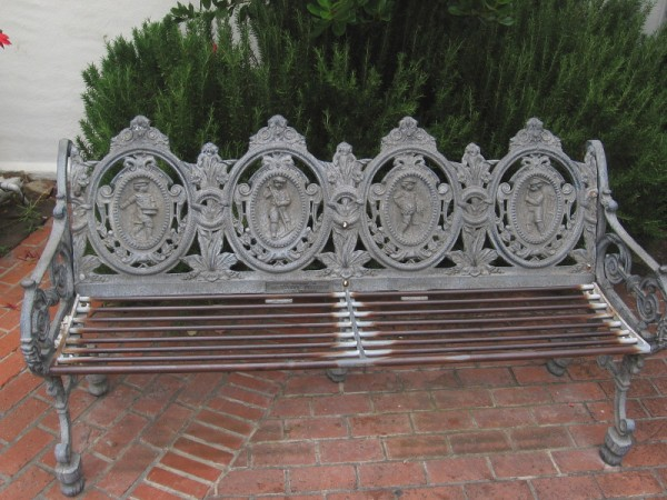 An ornate bench in the courtyard outside the rotunda of the Athenaeum Music and Arts Library. A small plaque on the bench reads In Memory of Genevieve Ferguson from Friends.
