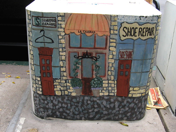 One of three similarly painted electrical boxes in a row. An artist's folksy rendition of La Jolla shops.