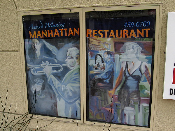 Stylish, jazzy posters on a building advertise the Manhattan of La Jolla restaurant.