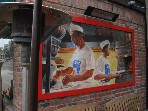 Small mural on the outdoor patio of Bernini's Bistro shows pizzas being prepared.