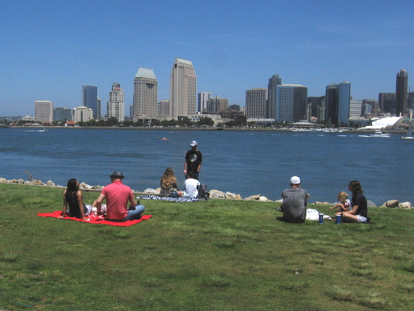 People sit on the grass at the Coronado Ferry Landing looking across San Diego Bay during the coronavirus pandemic.