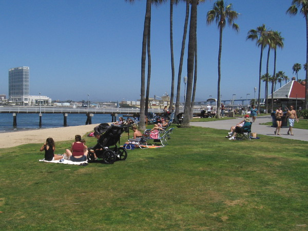 More people sit near the small beach at the Coronado Ferry Landing.