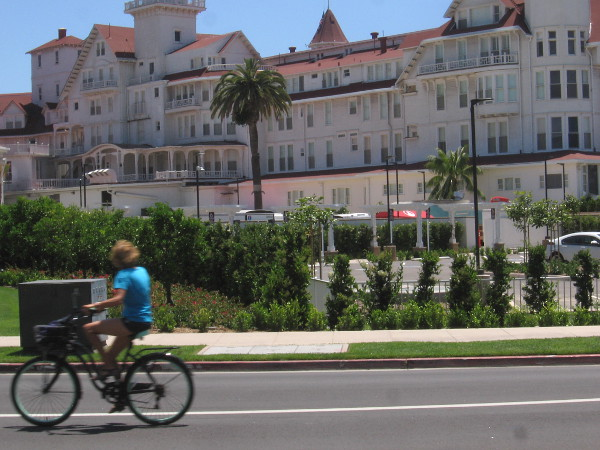Bicyclist heads down the street, with the Hotel del Coronado in the background.