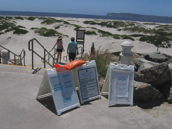 A couple heads down steps to the beach past signs concerning the latest coronavirus rules and regulations.