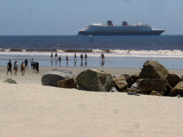 People walk along beautiful Coronado Beach. The immense Disney Wonder cruise ship is parked in the ocean off San Diego waiting for the health crisis to end.