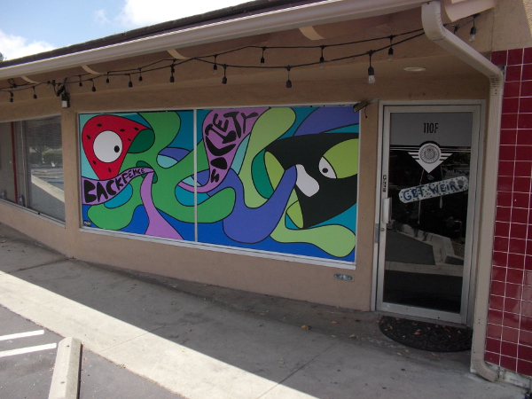 Crazy, colorful mural by front door of Backfence Society, where North County artists gather and create.