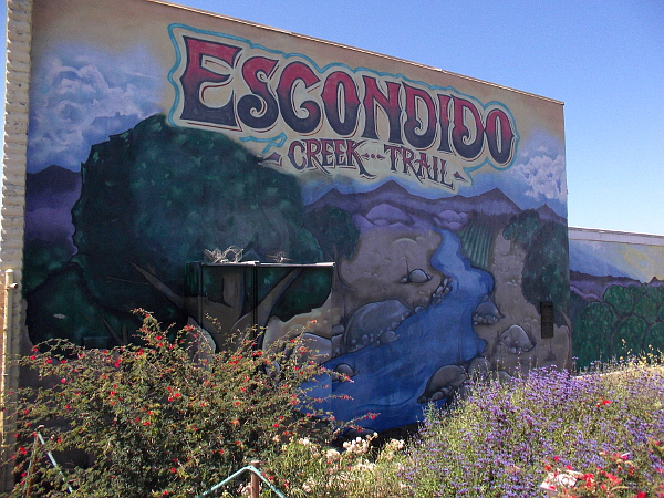 Escondido Creek Trail mural behind flowers by the popular bike and pedestrian path.