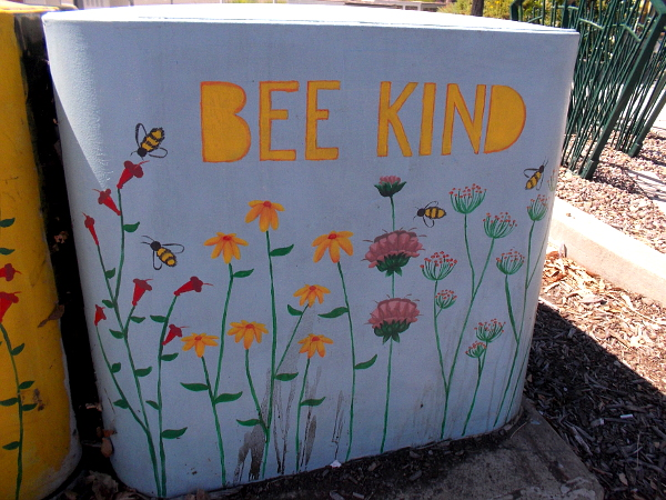 Another nearby electrical box reads BEE KIND.