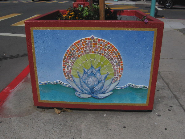Planter on sidewalk with tile mosaic depicting a lotus, symbol of divine beauty. The lotus is Vietnam's national flower.