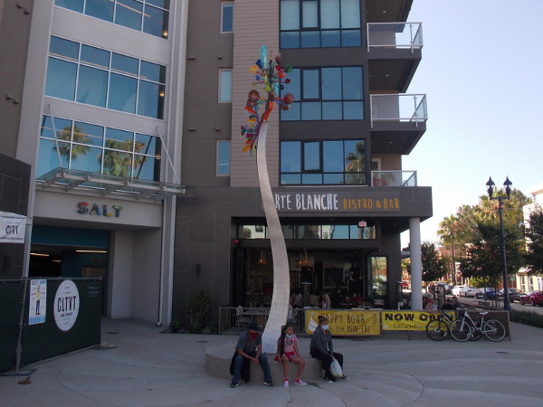 A tall, kinetic wind sculpture in Oceanside, California by artist Andrew Carson, in front of the SALT building.