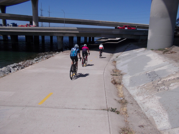 Bicyclists on Sweetwater Bikeway about to go under Interstate 5.